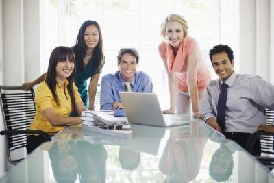 Smiling colleagues with laptop in a conference room.