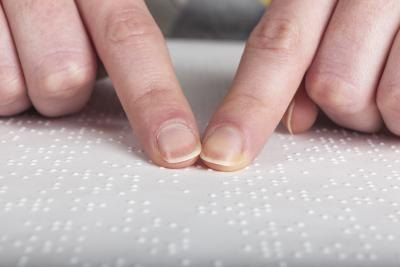 Fingers reading Braille book.