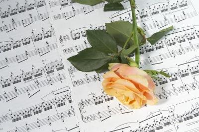 Rose on sheet music with song lyrics.