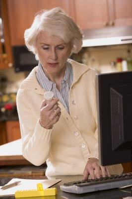 Woman looking at prescription and typing on computer