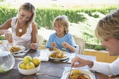 Boy eating at table with parents outdoors