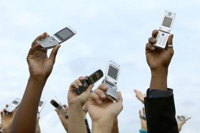 people holding up old cell phones