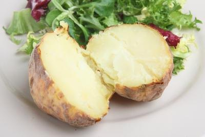 A plain baked potatoe with salad.