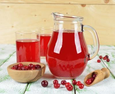 Pitcher and glasses filled with cranberry juice as well as a bowl of cranberries on a table