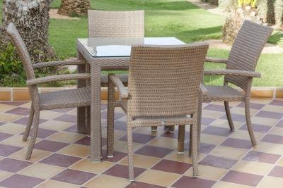 A table for four in an outdoor room with ceramic tile flooring.
