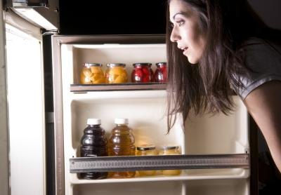 A woman looking into a refrigerator at night