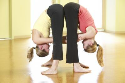 Two women do wide leg forward bend together at a studio.