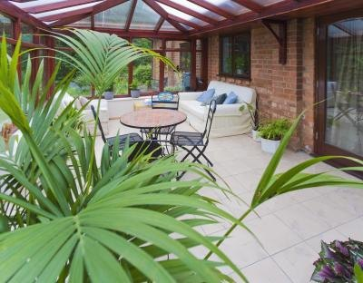 A sunroom with tile flooring, a patio table, living room furniture and plants.