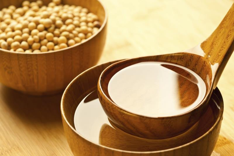 A small scoop of soybean oil, next to a bowl of soybeans.