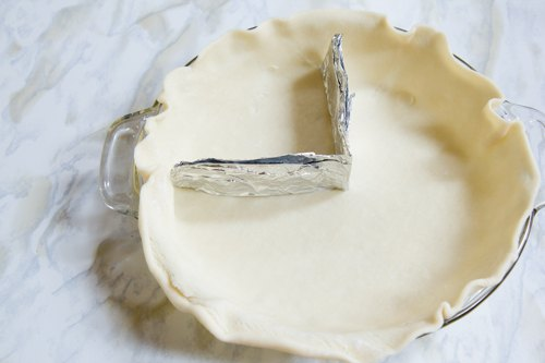 Fit aluminum foil into pie plate.