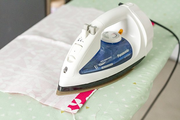 Activate the adhesive properties of the hem tape by moving a heated iron over the folded fabric.