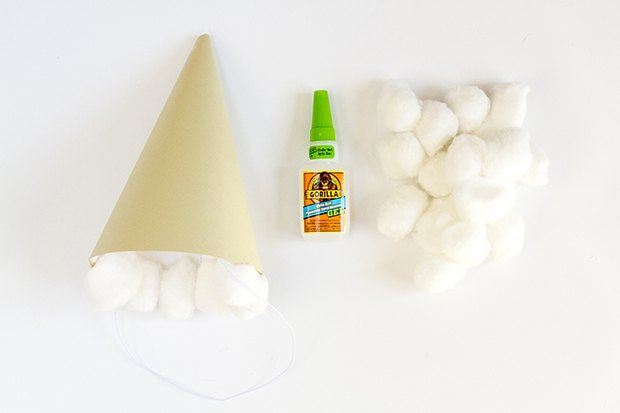 Use glue to attach cotton balls to the rim of the paper hat to mimic ice cream scoops.