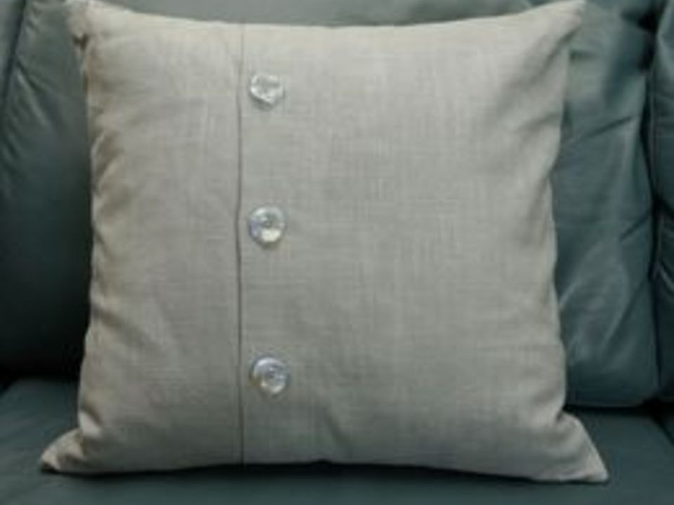 Envelope-back pillow with decorative buttons.