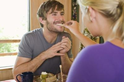 A woman gives a man a bite of food.