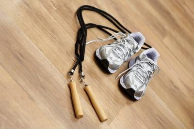 A close-up of cross training shoes and a jump rope on a wood floor.