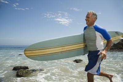 An older man run with a surfboard.