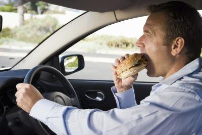 A man eats fast food in the car.