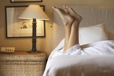 Woman lying on bed with feet up