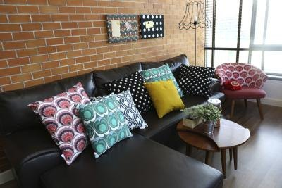 A black leather couch against a brick wall dressed with colorful pillows in a loft space.