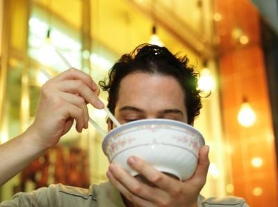 A close-up of a man eating noodle soup in a restaurant.