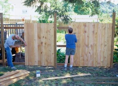 Family building a backyard fence