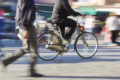 A person riding a bicycle and people walking in the street.