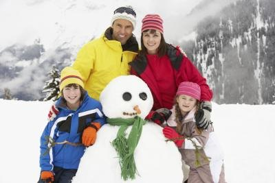 family making snowman on vacation