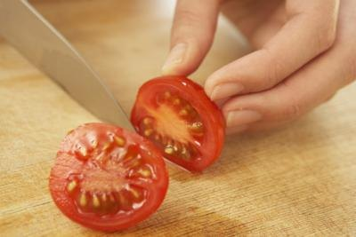Close-up of tomato being sliced on cutting board.
