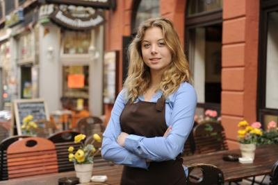 A waitress stands in front of outdoor tables.