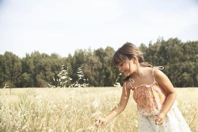 A girl standing in a wheat field.