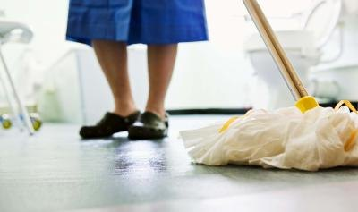 Woman mopping bathroom floor.