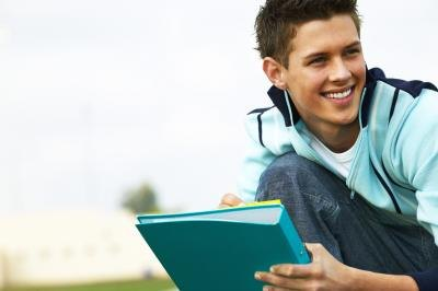 Teenage boy smiling with notebook