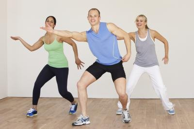 Three people doing zumba in a gym studio.