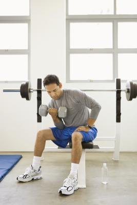 Seated dumbbell curls isolate the biceps muscles during each rep.