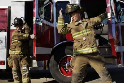 Two female firefighters exit a fire truck.