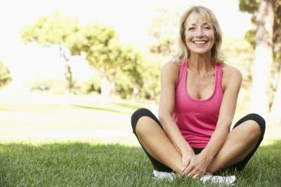 Healthy senior woman stretches in park