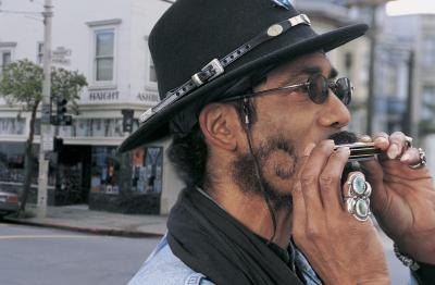 A man plays the harmonica while walking in the city.