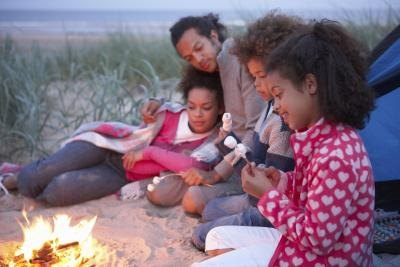 A family by the fire camping out on the beach.