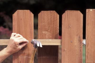 Hammering A Nail Into The Rail Of A Fence