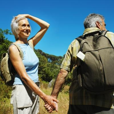 A mature couple takes a hike in the country side.