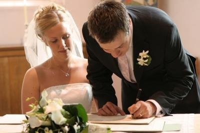 A newly wedded couple sign documents.