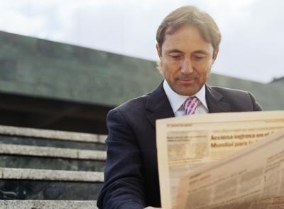 Businessman reading newspaper.