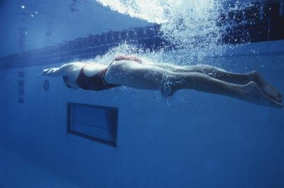 Woman pushing off wall in pool