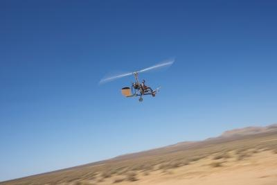 An ultralight flies over the desert.