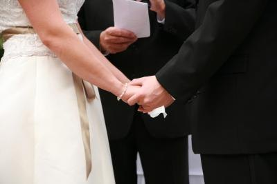 A bride and groom hold hands in front of a notary official.