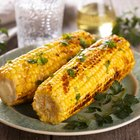 Roasted corn on the cob sitting on wood serving dish
