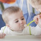 Little Caucasian baby eats with help of mother