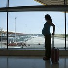Pregnant woman pulling a suitcase inside airport