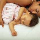 Mother putting her daughter to bed