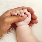 Father's hands holding his newborn with love,